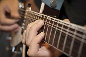 Close Up Shot Of A Man With His Fingers on the Frets of Guitar Playing