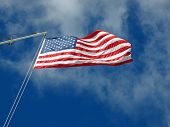 image of wispy  - The American Flag Waving Before Wispy Clouds and a Blue Sky - JPG