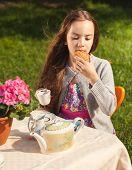 Beautiful Girl Having Breakfast At Yard And Biting Cookie