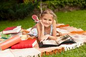 stock photo of keepsake  - Portrait of happy girl lying on plaid at park and looking at family album - JPG