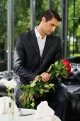 Handsome man with bunch of red roses waiting his lady in restaurant