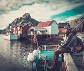 Man traveller sitting on a pier in Reine village, Norway