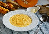 picture of porridge  - corn porridge with pumpkin in white plate on the wooden white  background - JPG
