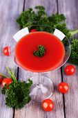 Tomato juice in goblet, parsley and fresh tomatoes on wooden background