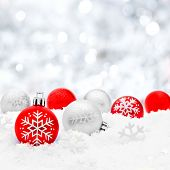 picture of twinkle  - Red and silver Christmas baubles in snow with twinkling silver background