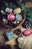 stock photo of gift basket  - Vintage Christmas decorations and pine cones in a wicker basket Christmas gift on a wooden table - JPG