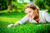 Close-up portrait of a beautiful smiling woman lying on a grass outdoor. She is absolutely happy.