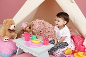 stock photo of tent  - Toddler child kid engaged in pretend play with food stuffed toys and teepee tent - JPG