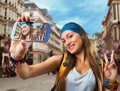 Happy traveler woman is taking selfie