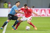 KLAGENFURT, AUSTRIA - MARCH 05, 2014: Aleksandar Dragovic (#3 Austria) and Luis Suarez (#9 Uruguay) fight for the ball in a friendly soccer game between Austria and Uruguay.