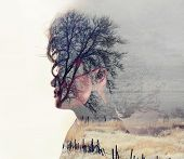 a serious looking woman side profile toned with vintage tones for a retro look and a double exposure with a field and trees