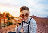 Young Bold Girl Woman In Hipster Clothes, Sitting On Roof Showing Off Tongue Looking Above Sunglasse