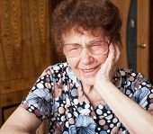 Old woman. Laughing elderly female at home
