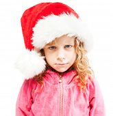 Sad girl in santa hat. Child isolated on white