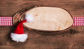 Rustic wooden christmas card or billboard with santa hat and red white checkered bow.