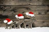 Three reindeer wearing santa hats on brown wooden background.