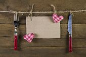 Cutlery in red color with empty advertising board and two red white checkered hearts on the background.