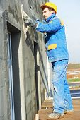 picture of putty  - builder worker plastering facade industrial building with putty knife float - JPG