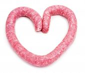 an uncooked pork meat sausage forming a heart on a white background