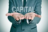 the word capital in the open hands of a businessman