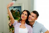 Portrait of a young beautiful couple making selfie photo with smarphone
