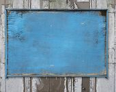 Old Blue Blank Weathered Wood Noticeboard On Rough Dirty Wall