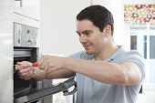 Repairman Fixing Domestic Oven In Kitchen