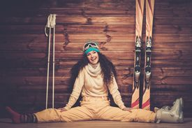 picture of ski boots  - Happy woman with skis and ski boots sitting near wooden wall  - JPG