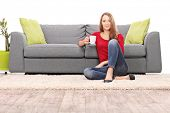 stock photo of early 20s  - Woman drinking coffee seated by a modern sofa isolated on white background - JPG