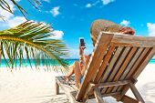 stock photo of palm-reading  - Young woman in hat with mobile phone at the beach - JPG