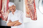 stock photo of slaughterhouse  - Portrait of happy mature butcher with arms crossed standing in slaughterhouse - JPG
