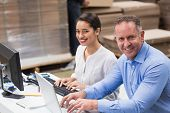 picture of warehouse  - Warehouse managers working with laptop at desk in a large warehouse - JPG