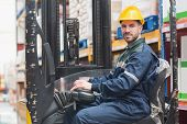 pic of forklift driver  - Portrait of driver operating forklift machine in warehouse - JPG