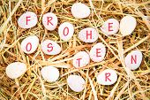 picture of easter candy  - frohe ostern against little candy easter eggs on straw - JPG