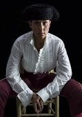 image of bullfighting  - Woman bullfighter sitting on a chair holding a rosary on a black background - JPG