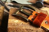 image of leather tool  - Craft tools with leather belt on table close up - JPG