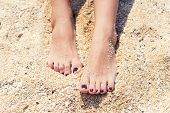 foto of pedicure  - female feet with pedicure in beach sand - JPG