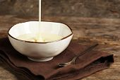 stock photo of condensation  - Bowl with condensed milk on napkin on wooden background - JPG