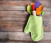 image of kitchen utensils  - Set of kitchen utensils in mitten on wooden planks background - JPG