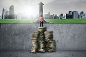 picture of past future  - Businessman standing on the stack of textbook to past the obstacle and look at the city - JPG