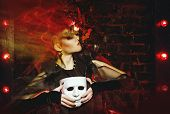 foto of witch  - Halloween witch with an unusual makeup and headdress of bats holding a mask - JPG
