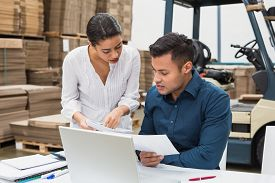 stock photo of warehouse  - Warehouse managers working with laptop at desk in a large warehouse - JPG