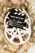 stock photo of mm  - Cinema movie reel and clapper board with 35 mm unrolled filmstrip background vertical frame - JPG