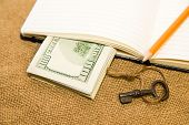 foto of memento  - Opened notebook with a blank sheet key and money on the old tissue - JPG