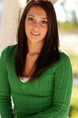Attractive young woman with beautiful brown straight hair and smile.