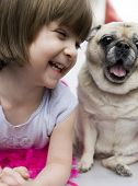 A lovely adorable young child with sweet smile looking at her pet pug dog