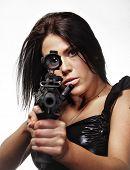 Woman looking through the site of a gun