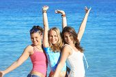 3 teens posing on beach