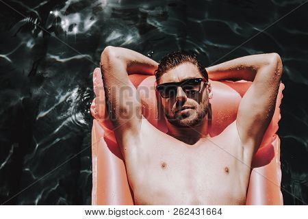 poster of Young Handsome Man In Sunglasses On Air Mattress. Attractive Bearded Man Wearing Sunglasses Relaxing