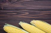 Fresh Corn On A Brown Wooden Table. Sweet Corn On A Brown Wooden Background poster